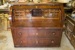 A mahogany roll top bureau before restoration